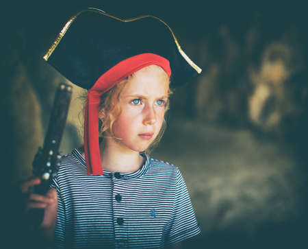 female pirate: Little girl in pirate costume with musket gun near the cave entrance. Place for your text.