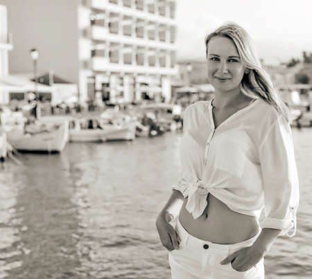 yacht people: Pretty woman standing against port with yachts. Black and white.