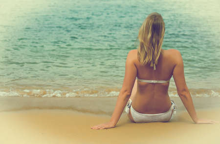 anonym: Woman sitting on the beach. Back view.