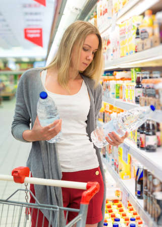 Woman choosing mineral water in grocery store.