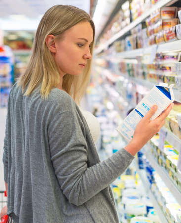 grocery shelves: Woman choosing milk in grocery store.