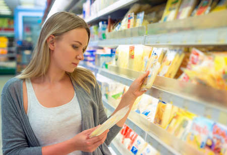 grocery shelves: Woman choosing cheese in grocery store.