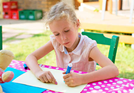 assiduous: Cute little girl drawing with marker pen.