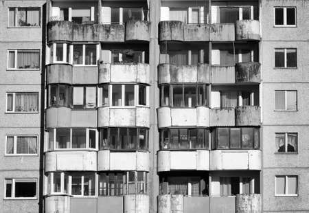 misery: Dirty facade with balconies and windows. Black and white.