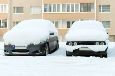 snowed: Cars covered with snow on the street in winter.