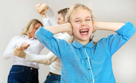 Parents quarreling at home, child is screaming. Stock Photo