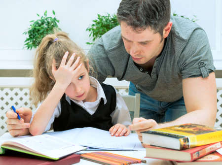 schoolwork: Father helping daughter with homework at home.