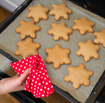 christmas baker's: Woman hands with heart shaped cookies.