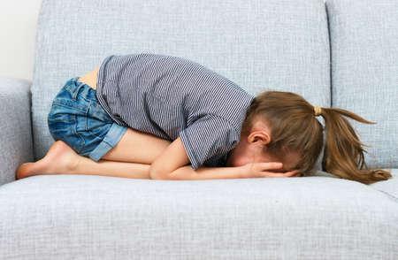 fille qui pleure: Sad petite fille qui pleurait sur le canapé.
