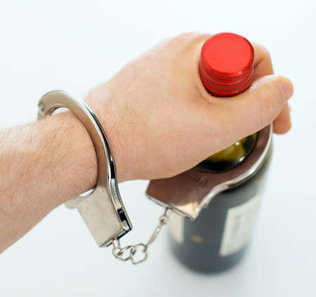 irresponsible: Hand handcuffed to bottle of wine. Alcoholism concept.