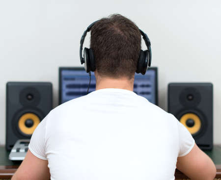 remix: Male sound producer in recording studio. Back view. Space for your text.