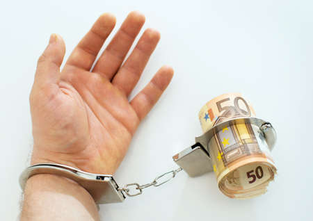 bribery: Hand with handcuffs and money. Bribery concept.
