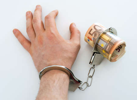 venality: Hand with handcuffs and money. Bribery concept.