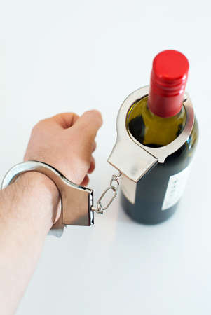 alcoholismo: Mano esposado a la botella de vino. Concepto del alcoholismo.