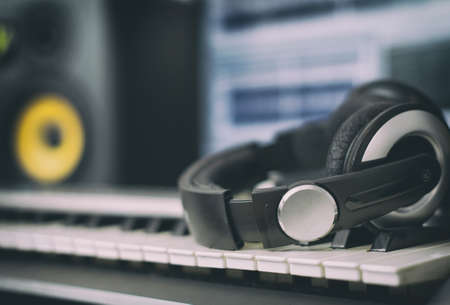 audio: Audio earphones. Home recording studio with professional monitors and midi keyboard.