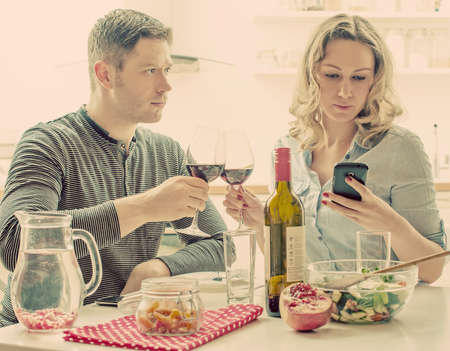 uninterested: Young couple having dinner at home. Modern relationships. Stock Photo