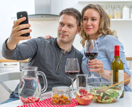 taking a wife: Young couple having dinner at home. Taking selfie with mobile phone.