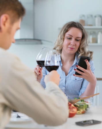 antisocial: Young couple having dinner at home. Modern relationships. Stock Photo