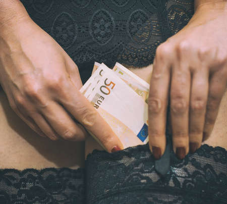 nude black girl: Prostitute hiding money in her stockings. Close-up view.