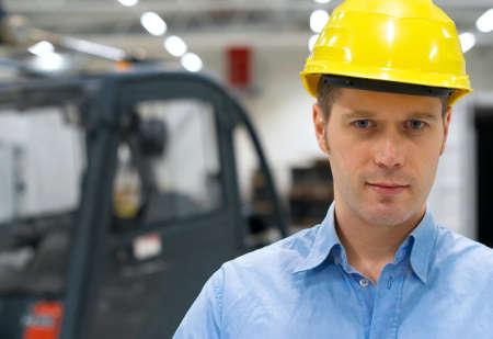 warehouseman: Warehouseman in yellow hard hat at warehouse.