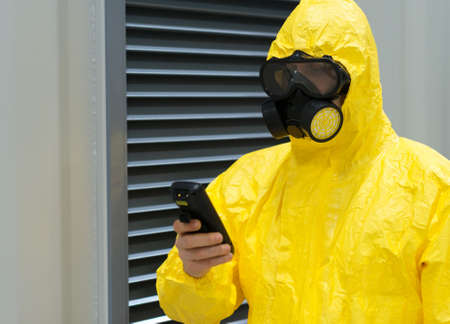 protective: Worker in protective chemical suit checking radiation with geiger counter. Stock Photo