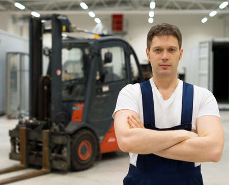 Handsome forklift operator in the warehouse.
