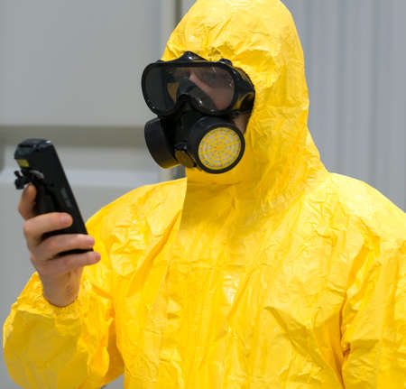 Trabajador en traje de protección química radiación con contador Geiger de cheques.