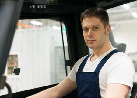 forklift driver: Handsome forklift operator working in the warehouse. Stock Photo