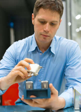 electronics industry: Handsome worker assembling electronic components at the factory.