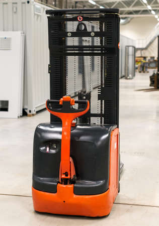 mini loader: Orange forklift loader in the modern warehouse.