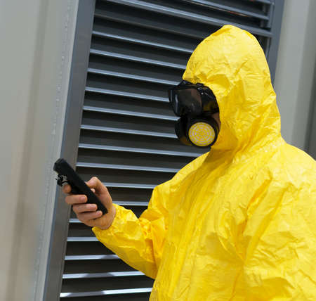 gamma radiation: Worker in protective chemical suit checking radiation with geiger counter. Stock Photo