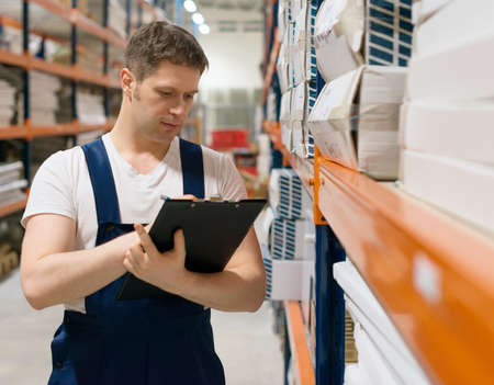 supervisor: Supervisor with clipboard checking barcode at the warehouse. Stock Photo