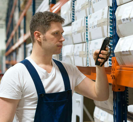warehouseman: Supervisor scanning package barcode at the warehouse.
