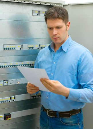 manual test equipment: Handsome man with manual near electrical industrial panel.