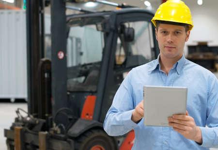 warehouseman: Warehouseman in hard hat with tablet pc at warehouse.