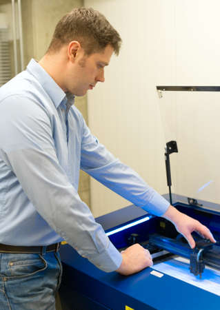 Handsome worker near desktop laser engraving machine.