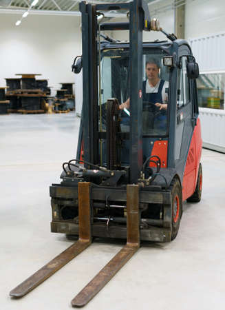 warehouseman: Handsome forklift operator working in the warehouse. Stock Photo
