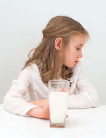 petite fille triste: Sad little girl avec un verre de lait. Banque d'images