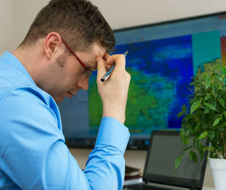 newscast: Handsome male meteorologist in glasses thinking. Stock Photo