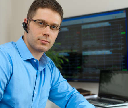 stock trader: Handsome stock trader in front of computer.