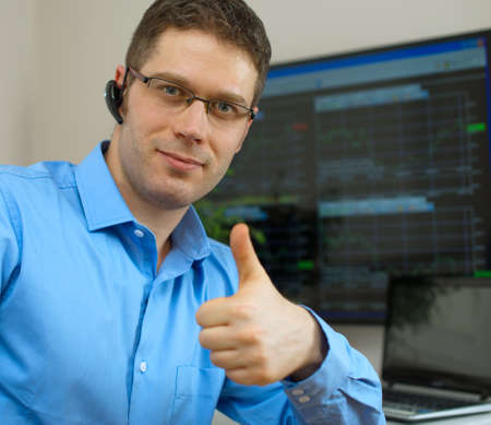 stock trader: Handsome stock trader with thumbs up in front of computer.
