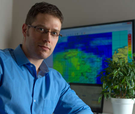 meteorology: Handsome male meteorologist in glasses on his workplace.