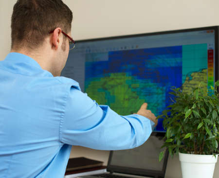 Handsome male meteorologist working with touchscreen.