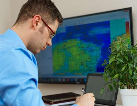 meteorólogo masculino hermoso en vidrios en su lugar de trabajo.