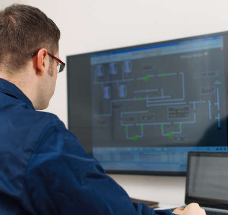 computer screens: Male worker in glasses in thermal plants control room.