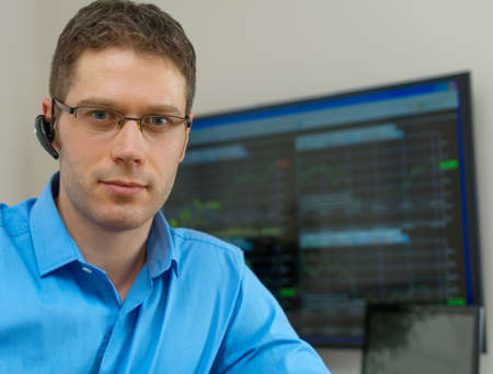trader: Handsome stock trader in front of computer.