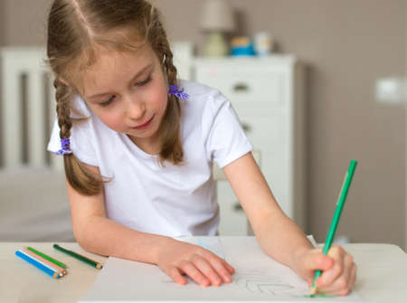 left handed: Little girl drawing with pencil at home.