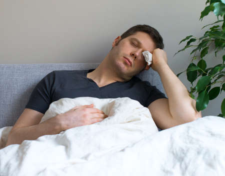Sick man lying in the bed with fever. Stock Photo