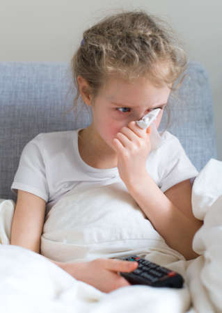 watching tv: Little girl blowing her nose while watching TV at home. Stock Photo