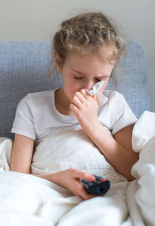 blowing nose: Little girl blowing her nose while watching TV at home. Stock Photo